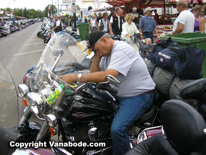 guy sleeping on motorcycle at sturgis motorcycle rally
